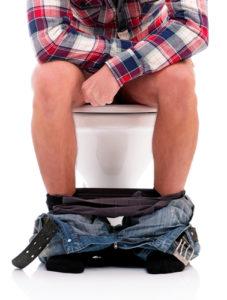 Mann auf Toilette hat schwarzen Stuhlgang