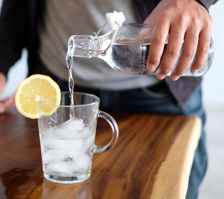Frau schenkt sich ein Glas Wasser ein wegen Sodbrennen in der Schwangerschaft