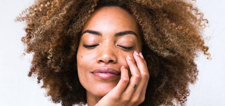 Frau pflegt ihre Haut im Gesicht mit CBD